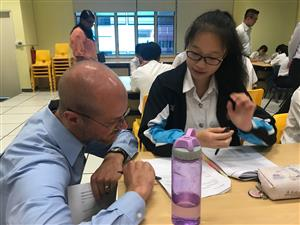 Mr. Davis meeting one-one-one with student in Singapore